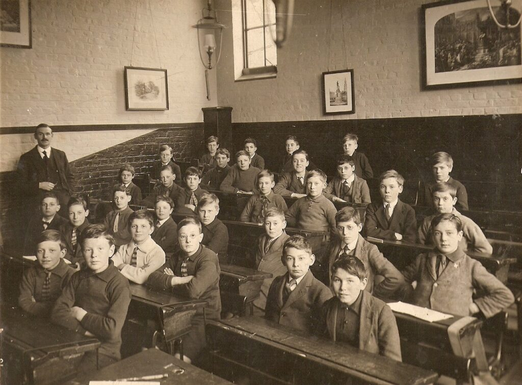 A large group of students sitting in a classroom learning at school from a good teacher  https://upload.wikimedia.org/wikipedia/commons/6/63/Classroom_-_England_-_1920s%3F_-_B%26W.jpg