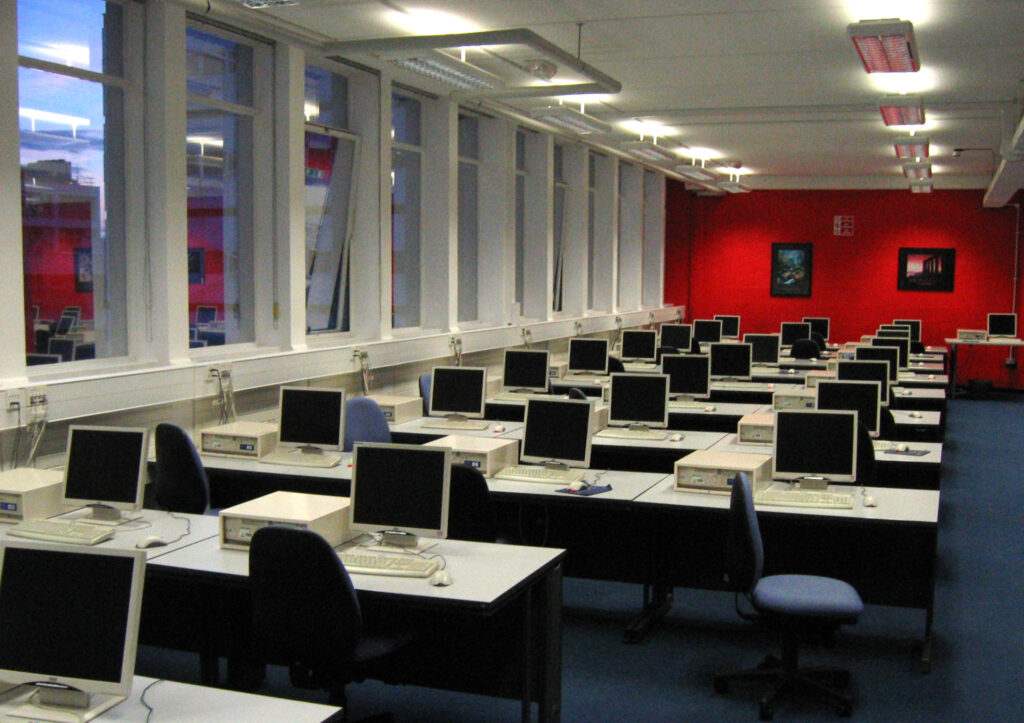 Computers set up for a hackathon are in a room waiting for the participants to begin working on the software engineering projects that they can then use to write a fantastic resume  https://upload.wikimedia.org/wikipedia/commons/4/40/Computer_lab_showing_desktop_PCs_warwick.jpg
