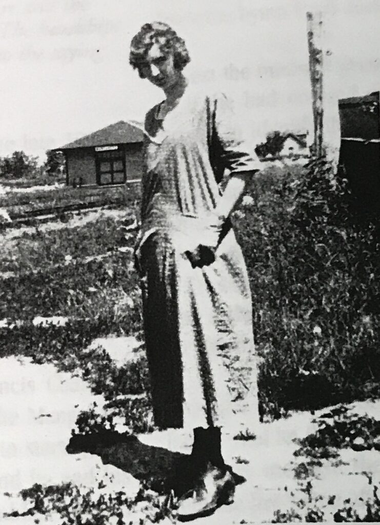 a newly graduated teacher or student teacher stands outside a school ready to teach students because she is educated and has a passion for teaching  https://upload.wikimedia.org/wikipedia/commons/4/47/School_Teacher_Anna_Dugan_and_Manganese_Minnesota_Depot.jpg