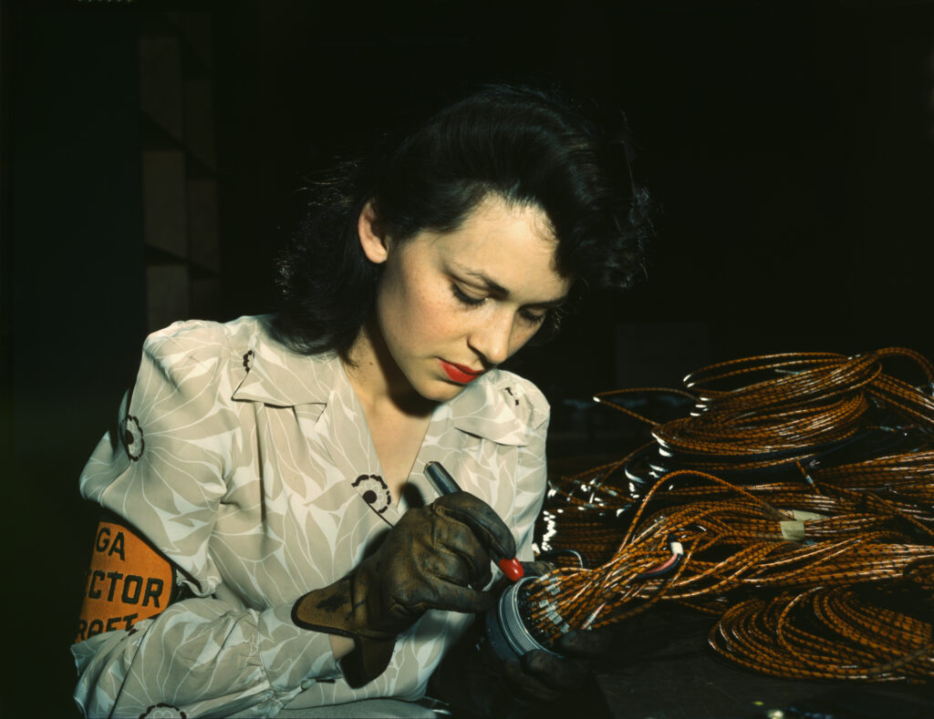 A woman, possibly a college student, works at her job of putting together airplanes for a good company during World War II  https://upload.wikimedia.org/wikipedia/commons/d/d1/World_War_II_woman_aircraft_worker%2C_Vega_Aircraft_Corporation%2C_Burbank%2C_California_1942.jpg