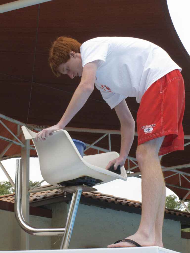 A lifeguard at a pool takes a break from saving lives to clean a chair to help maintain good pool and water safety and do his job well  https://upload.wikimedia.org/wikipedia/commons/c/c3/Brian_Delaney%2C_a_lifeguard%2C_cleans_a_lifeguard_observation_chair_at_a_swimming_pool_during_preparations_for_the_2010_swimming_season_at_Randolph_Air_Force_Base%2C_Texas%2C_May_20%2C_2010_100520-F-SS509-005.jpg