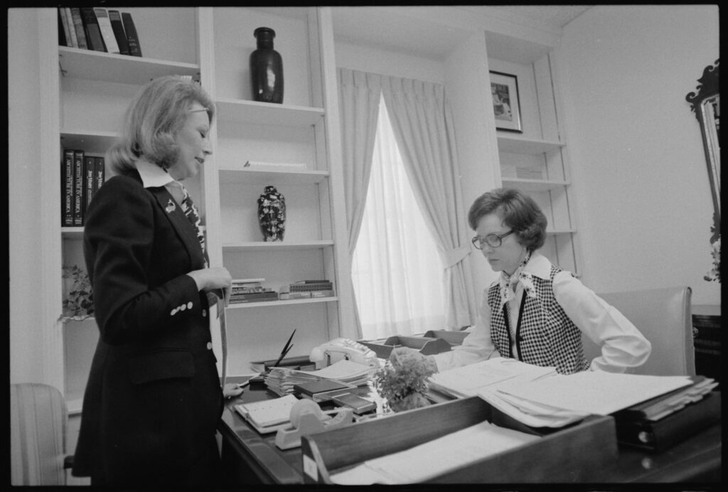 A personal assistant providing assistance to her boss who needs help with many tasks including paperwork and scheduling  https://upload.wikimedia.org/wikipedia/commons/1/1b/Rosalynn_Carter_with_her_personal_assistant%2C_Madeline_McBean._-_NARA_-_174076.jpg